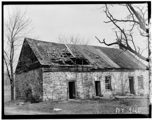 Black and white photo of delapidated one story building with broken roof