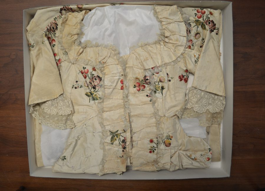 Archival box displaying folded up ivory dress with enboded flowers and berries