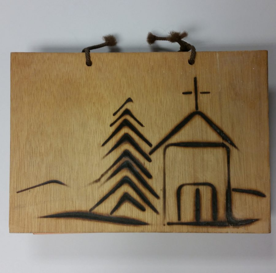 Wood burned cover of a cookbook with a tree and an church represented.