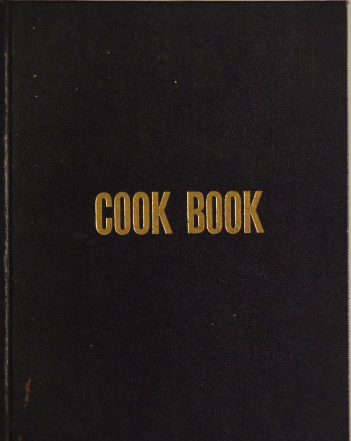 "Black cover of a cookbook that simply treads ""Cook Book"""