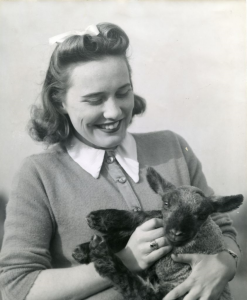 1950s photograph of a woman holding a lamb.
