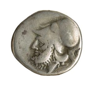Didrachm coin minted between 280 B.C.E.-276 B.C.E.  An unevenly round coin with a profile of a man's face with a cap.