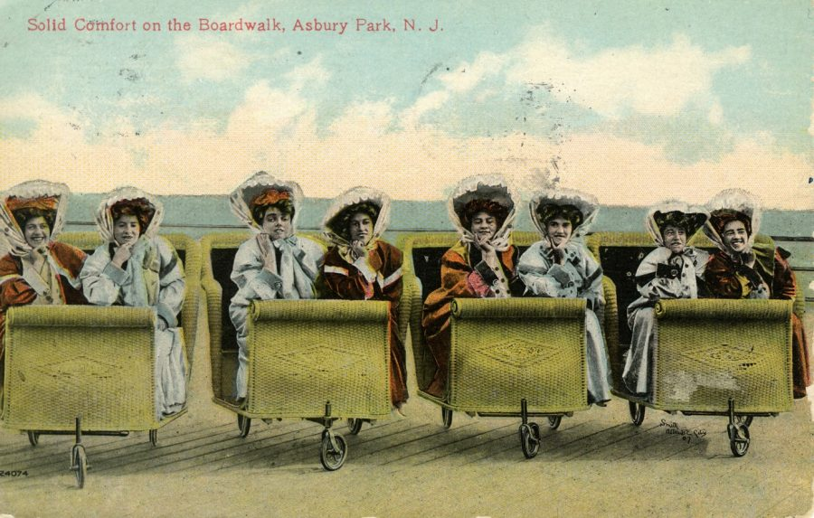 "Colored Postcard showing eight women with hats on beach chairs on wheels with heading ""Solid comfort on the boardwalk, Asbury Park, N.J."""